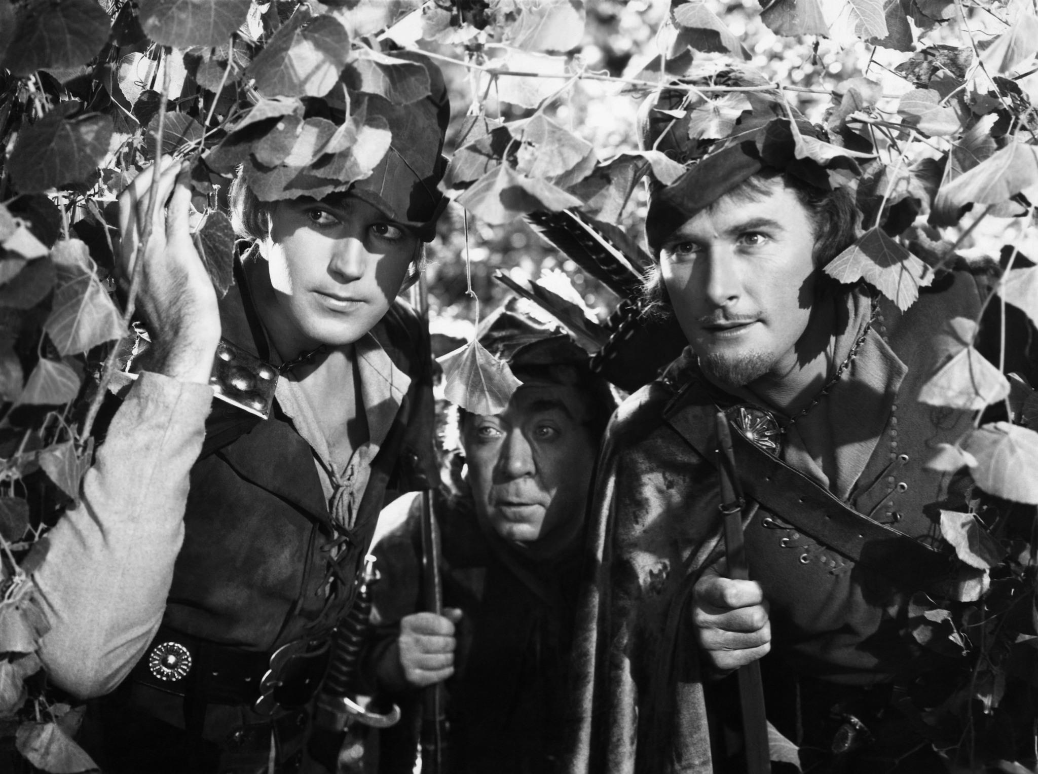 still-of-errol-flynn,-patric-knowles-and-herbert-mundin-in-the-adventures-of-robin-hood